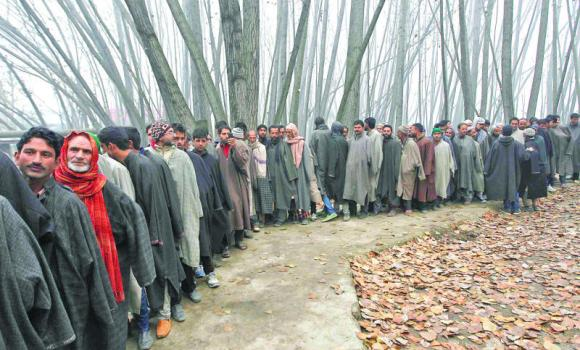 Voters line up to cast their votes outside a polling station during the first phase of the Jammu and Kashmir state assembly elections at Dangarpora on Tuesday.