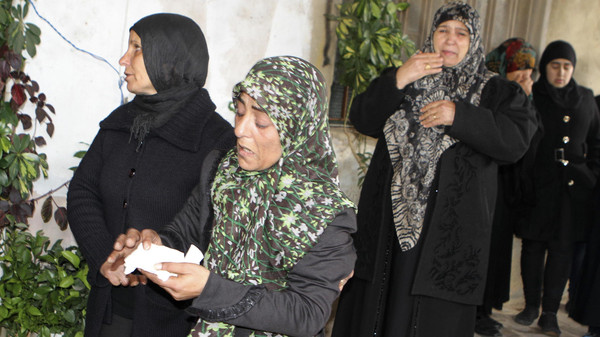 The mother (C) and family members of Lebanese soldier Ali al-Bazzal, who was killed by Syria's al Qaeda offshoot Nusra, mourn his death in his hometown Bazalia village December 6, 2014.