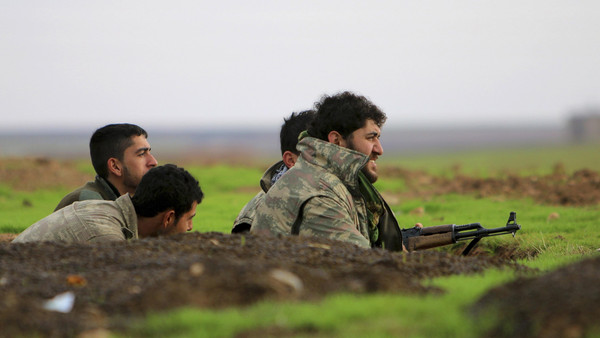 Fighters of the Kurdish People's Protection Units (YPG) take positions in a trench at the frontline against ISIS fighters in the southern countryside of Ras al-Ain December 7, 2014.