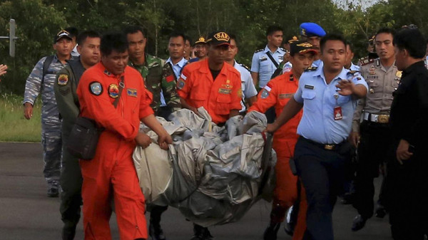 Members of the Search and Rescue Agency carry debris recovered from the sea presumed from missing Indonesia AirAsia flight QZ 8501.