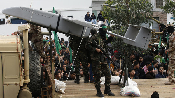 Palestinian members of al-Qassam Brigades, the armed wing of the Hamas movement, display a home-made drone during a military parade marking the 27th anniversary of Hamas' founding, in Gaza City Dec. 14, 2014.