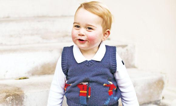 Prince George poses for a photograph in a courtyard at Kensington Palace, London.
