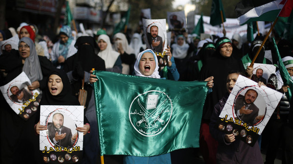 Protesters from the Islamic Action Front, carry pictures of the deputy overall leader of Jordanian Muslim Brotherhood Zaki Bani Rsheid during a demostration to show their solidarity with Palestinians and anger at the political arrest, after the Friday prayer in Amman November 28, 2014.