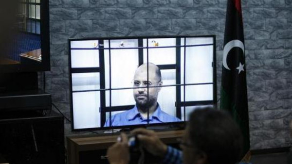 Seif al-Islam is seen on a screen via video-link in a courtroom in Tripoli as he attends a hearing behind bars in a courtroom in Zintan, April 27, 2014.