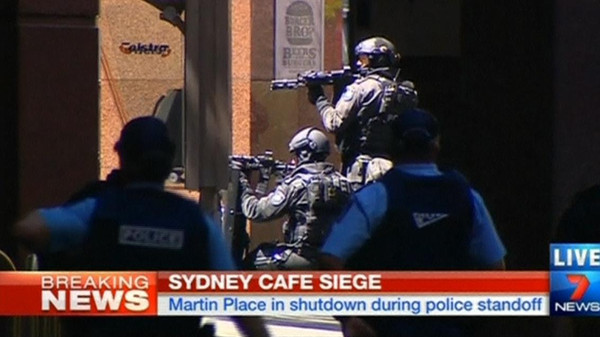 Television footage has shown a black flag with Arabic writing being held up in the cafe