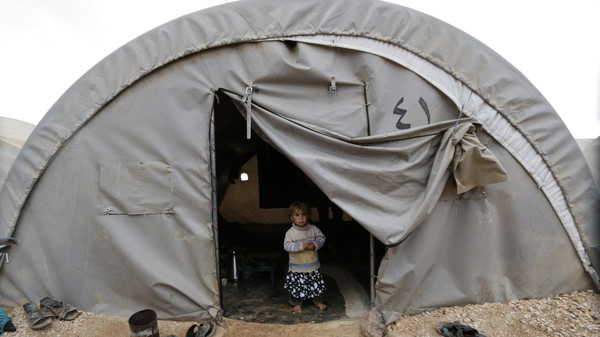 A child, who is internally displaced due to fighting between rebels and forces loyal to Syrian President Bashar al-Assad, peeks out from a tent at the Jarjanaz refugee camp in Idlib November 30, 2014.