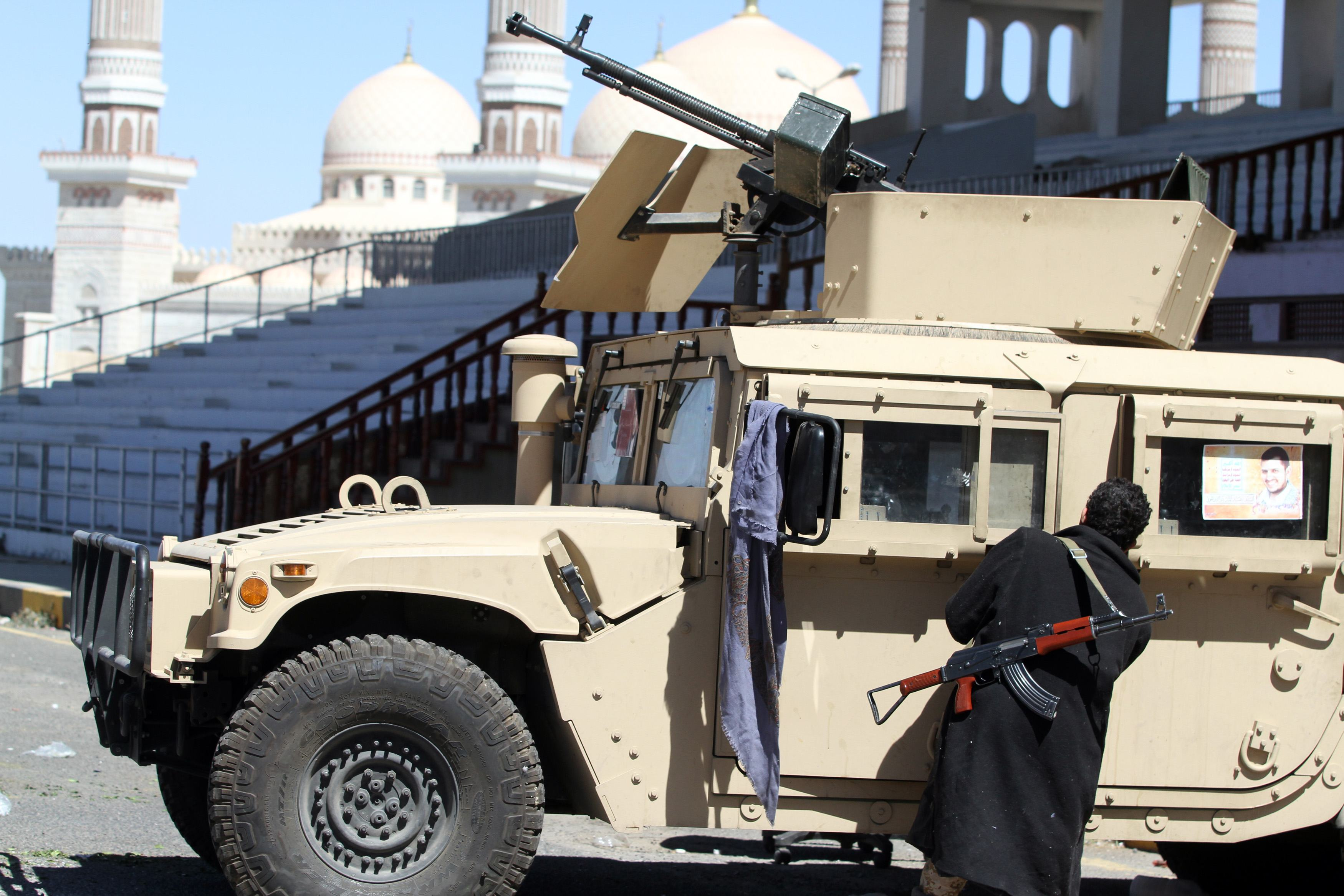 A Houthi fighter opens the door of a military vehicle which was seized from the army during recent clashes, outside an entrance to the presidential palace in Sanaa January 29, 2015.