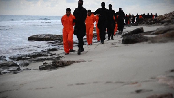 Men in orange jumpsuits purported to be Egyptian Christians held captive by the ISIS are marched by armed men along a beach said to be near Tripoli, in this still image from an undated video made available on social media on February 15, 2015.