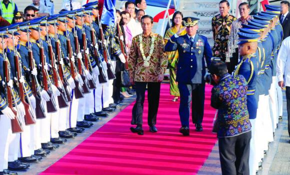 Indonesia's President Joko Widodo, center, walks with Philippine Lt. Gen. Jeffrey Delgado, center right, after his arrival at the airport for a state visit in Manila on Sunday.