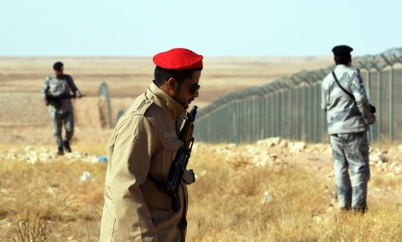 Members of the Saudi border guards patrol the fence on the Kingdom's northern border with Iraq, near Arar City, on Monday. Saudi Arabia increased its security measures along its frontier with Iraq following attacks launched by the Islamic State (IS) group against Saudi troops and security posts along the border.