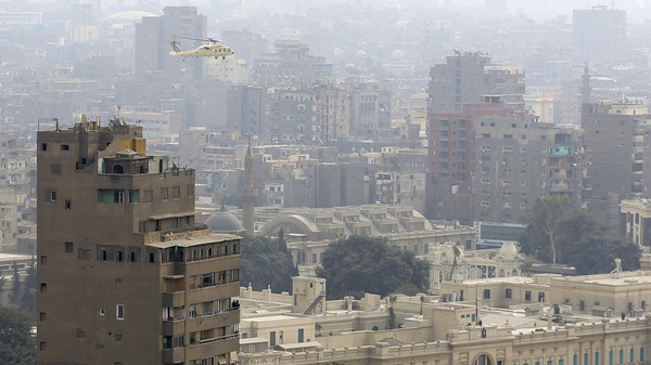 A reconnaissance military helicopter flies over Cairo.