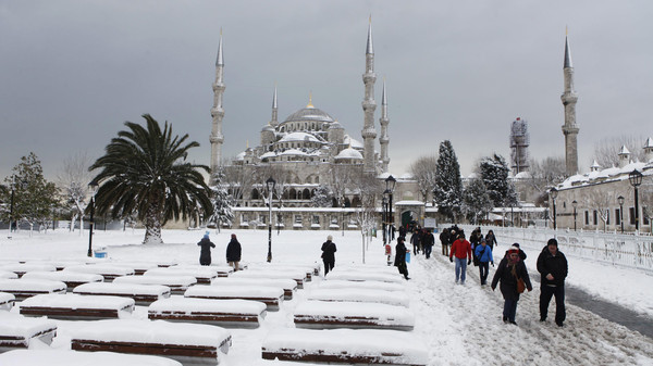Tourists stroll on the snow-covered Sultanahmet Square in the historic old town of Istanbul February 19, 2015.