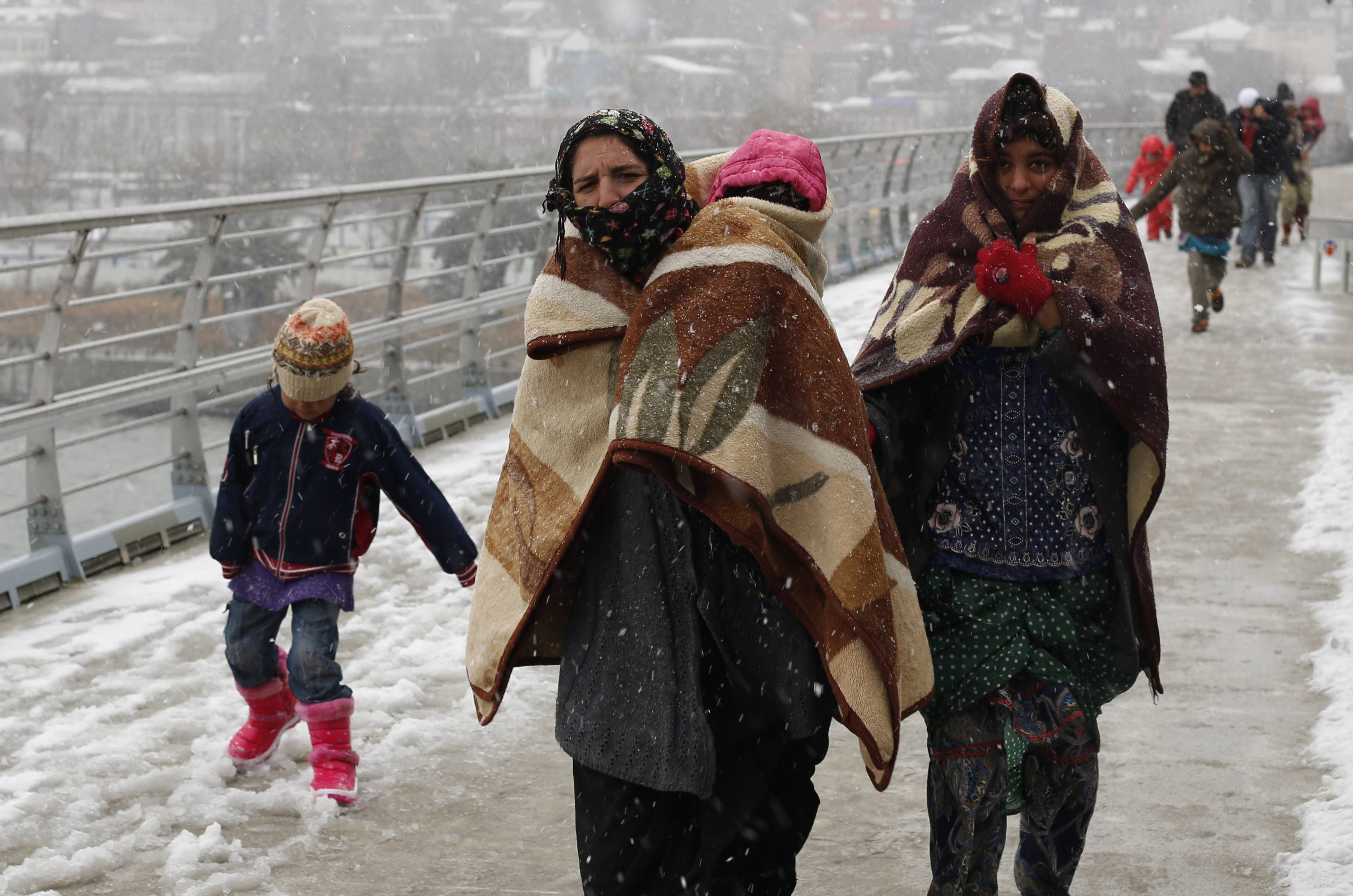 Syrian refugees brave the cold and snow as they walk to a metro station in Istanbul February 11, 2015, at the start of a day's begging.