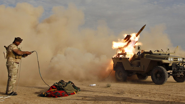 A Shi'ite fighter launches a rocket during clashes with Islamic State militants on the outskirts of al-Alam March 8, 2015.