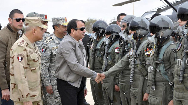 Egyptian President Abdel Fattah al-Sisi shakes hands with pilots and crews specialists of the Egyptian Air Force near the border between Egypt and Libya.