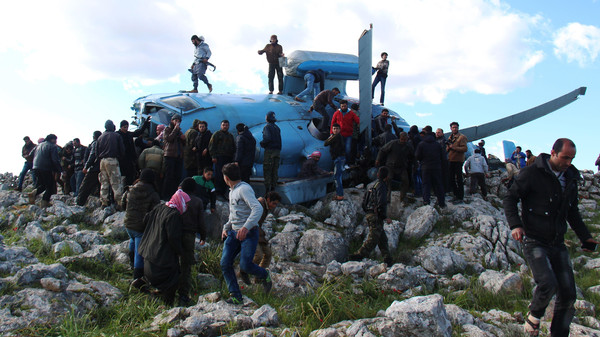 People gather around a helicopter reportedly belonging to the Syrian regime forces that crashed on March 22, 2015 in Jabal al-Zawiya in the northwest province of Idlib.