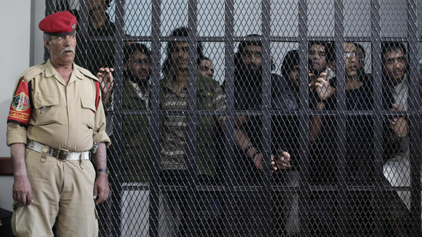 A Yemeni military policeman stands guard as suspected Yemeni militants stand behind bars during a court session at a state security court in Sanaa, Yemen.