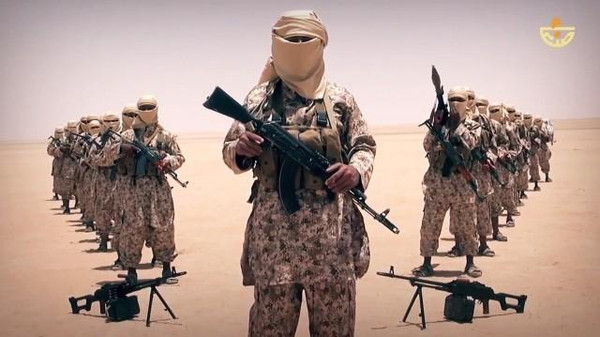 Alleged ISIS militants wear matching uniforms in a desert landscape. They vowed to target Houtihs in Yemen.