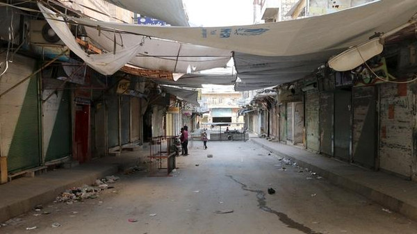 Civilians stand in front of closed shops in Idlib city.