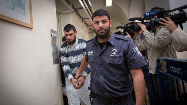 Police escort East Jerusalem resident Khaled Kutina to his hearing at the Magistrate's Court in Jerusalem.