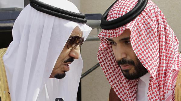 File photo shows King Salman bin Abdul-Aziz Al Saud (L) speaks with his son Prince Mohammed in Riyadh, Saudi Arabia.