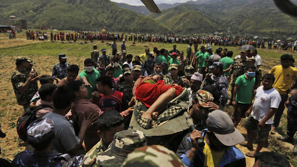 Nepalese soldiers carry a wounded woman to a waiting Indian air force helicopter as they evacuate victims of Saturday's earthquake from Trishuli Bazar to Kathmandu airport in Nepal, Monday, April 27, 2015.