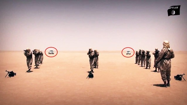 Late model vehicles are seen in the background of the Wilayat Sanaa training video shot in the desert of Yemen.