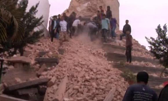 In this image from AP video people search in a buildings rubble in Katmandu, Nepal after a strong earthquake hit the area on Saturday.