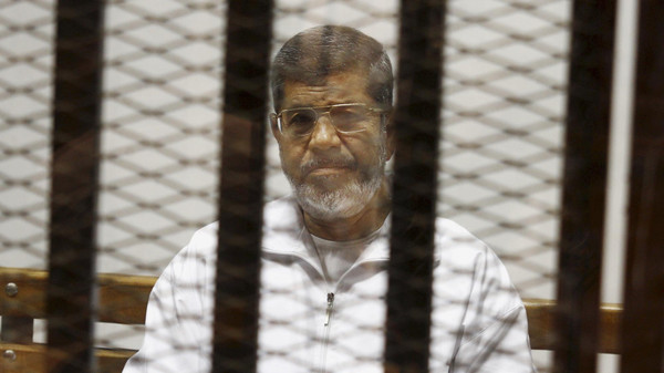 In this May 8, 2014 file photo, Egypt's ousted Islamist President sits in a defendant cage in the Police Academy courthouse in Cairo.