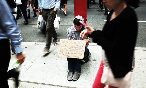 A homeless teen panhandles on a street near Eighth Avenue in Manhattan in New York City.