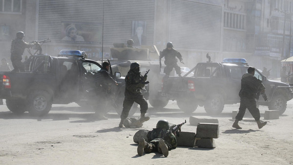 Afghan security forces run for the site of Afghan Justice Ministry following an attack in Kabul.