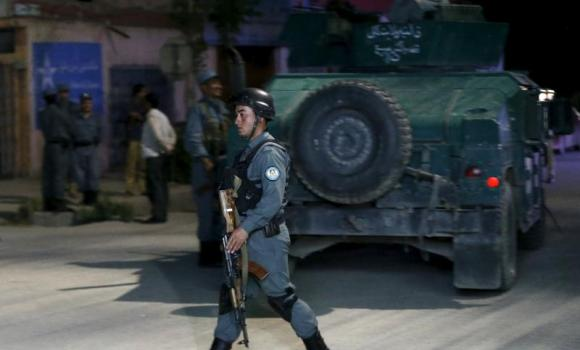 An Afghan policeman keeps watch at the site of an attack in Kabul.
