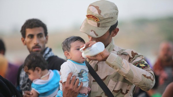 An Iraqi soldier carries a displaced kid from Ramadi at the outskirts of Baghdad, May 19, 2015.