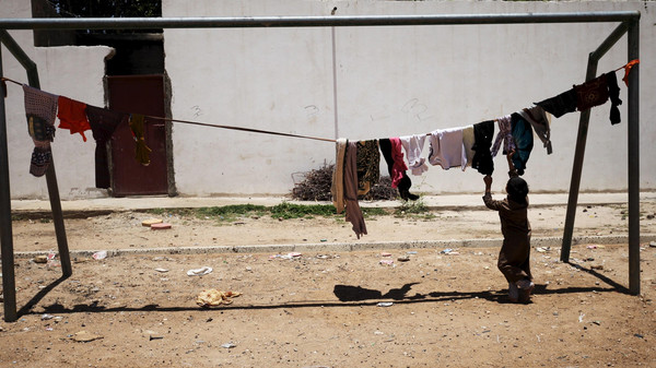 An internally displaced boy hangs laundry out to dry in a school playground in Sanaa.