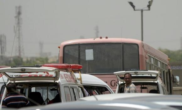 Residents stand beside a bus parked at a hospital following an attack by gunmen in Karachi.