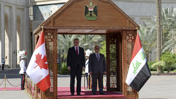 Canada's PM Harper takes part in a welcoming ceremony with Iraq's PM al-Abadi at the presidential palace in Baghdad.