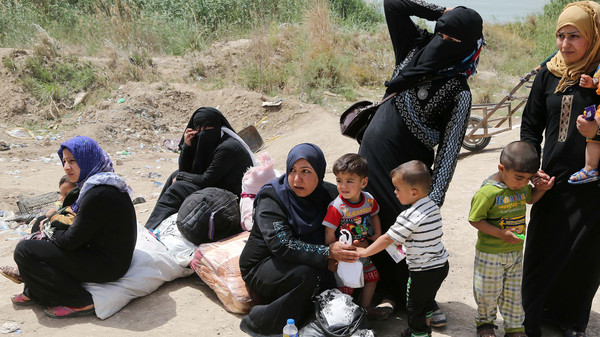 Displaced people from Ramadi wait to receive humanitarian aid from the United Nations World Food Programme at a camp in al-Shurta neighborhood in west Baghdad, Iraq, Thursday, April 23, 2015.