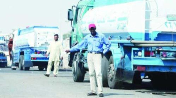 Expatriate workers offer to sell water in tankers to passersby outside the water distribution center in Jeddah.