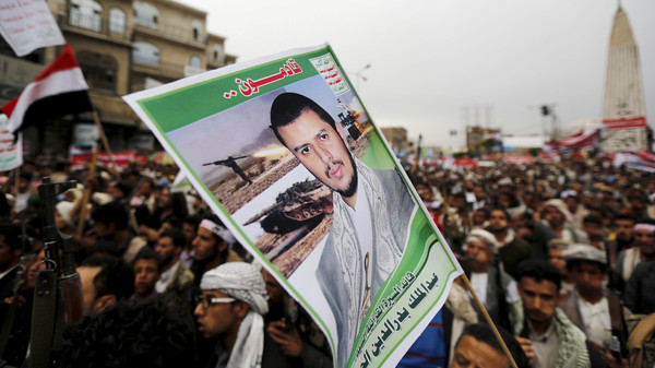 Houthi follower holds up a poster of leader of the Houthi group Abdul Malik Badruddin al-Houthi during a demonstration against the Saudi-led air strikes, in Sanaa.