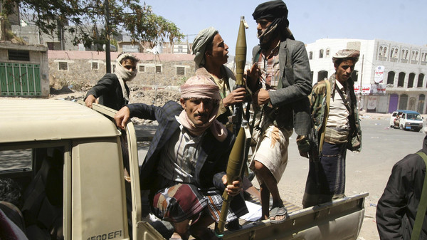 Members of the Popular Resistance Committee ride a truck as they secure a street during clashes with Houthi fighters in Yemen's southwestern city of Taiz.