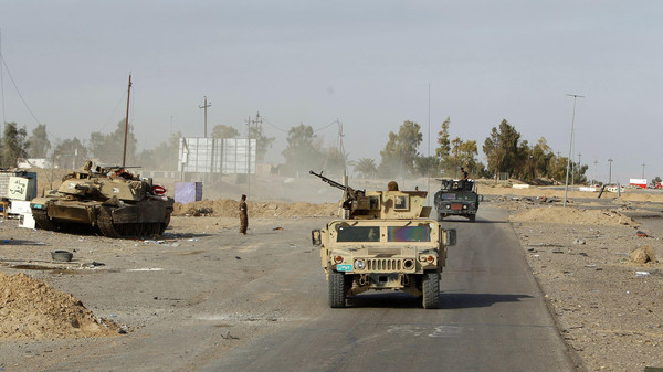 Military vehicles of Iraqi security forces make their way on the outskirts of Baiji, north of Baghdad.