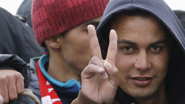 Moroccan citizen Touil Abdelmajid makes a victory sign as he arrives with migrants on the Italian navy ship Orione at Porto Empedocle harbour in Sicily.
