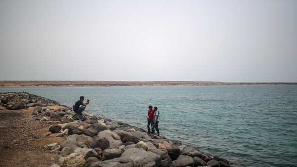 Newly-arrived Yemeni refugees take photos at the port in Obock, Djibouti, Tuesday, May 19, 2015, where they are processed by immigration police.