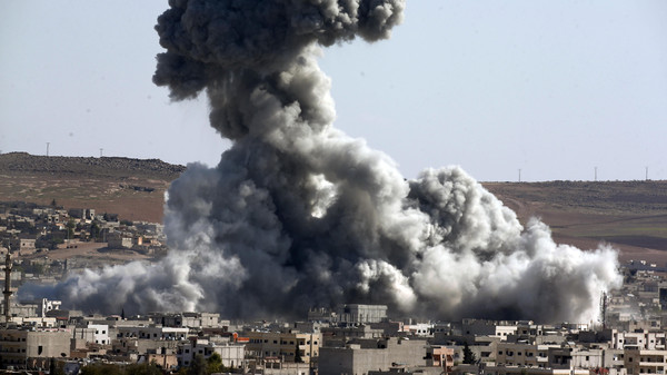 Smoke rises over the town of Kobani during airstrikes by the US led coalition, seen from the outskirts of Suruc, near the Turkey-Syria border, Wednesday, Oct. 29, 2014.