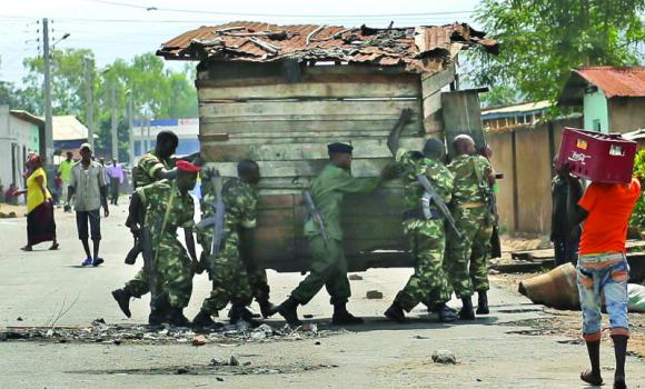 Soldiers remove a barricade set by demonstrators opposed to President Pierre Nkurunziza's bid for a third term in office, march in the Nyakabiga neighborhood of Bujumbura, Burundi, on Saturday.