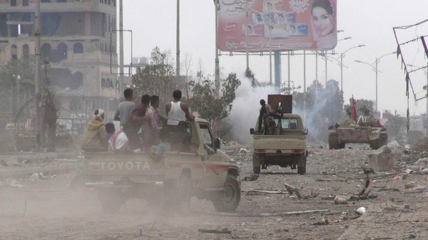 Southern Popular Resistance fighters advance along a street during fighting with Houthi fighters in Yemen's southern port city of Aden.