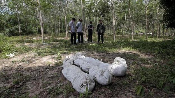 Thai policemen take notes behind human remains retrieved from a mass grave at a rubber plantation near a mountain in Thailand's southern Songkhla province on May 6, 2015.