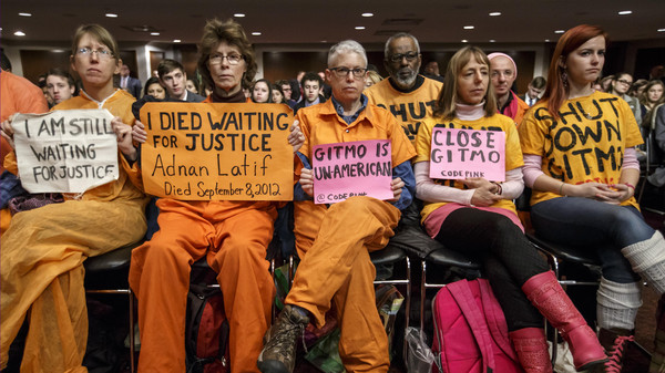 Activists from the antiwar group CodePink hold silent protest at the Senate Armed Services Committee during a hearing on the detention center in Guantanamo, Cuba, on Capitol Hill in Washington, Thursday, Feb. 5, 2015