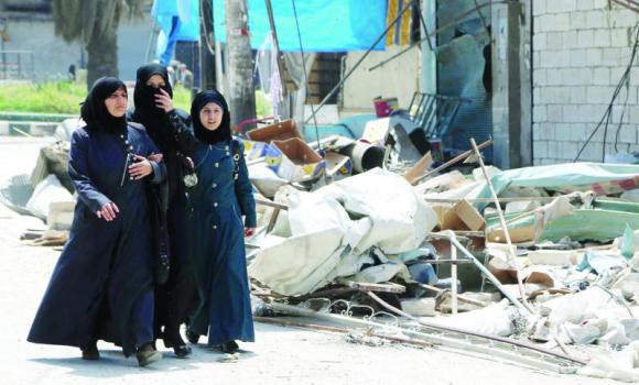 Women walk near a damaged building in Aleppo's Al-Saliheen district on Saturday.