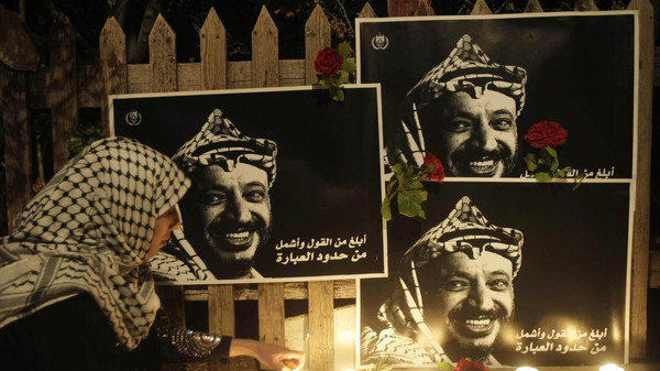 A Palestinian woman lights candles under posters of late Palestinian President Yasser Arafat.